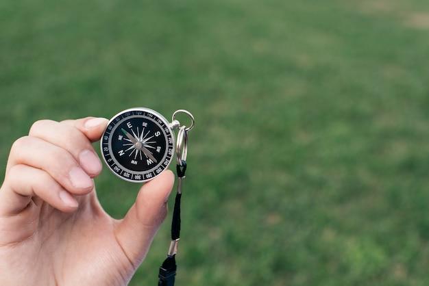 Zbliżenie Dłoni Trzymając Kompas Nawigacyjny Przeciwko Zielone Tło Zamazane Pole Darmowe Zdjęcia