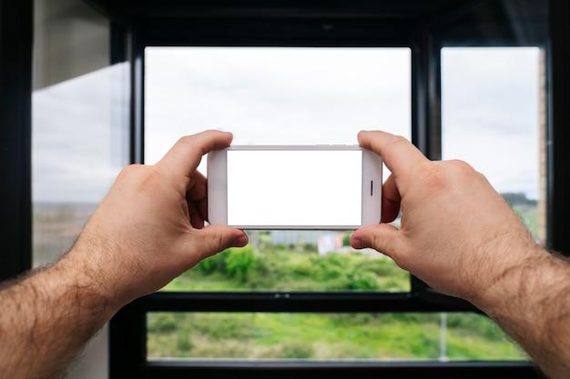Zbliżenie Dłoni Trzymającej Telefon Komórkowy, Aby Zrobić Zdjęcie Z Okna Domu Premium Zdjęcia