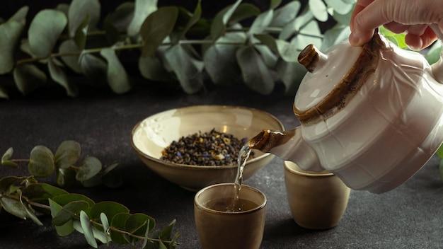 Zbliżenie Dłoni Wlewając Herbatę W Filiżance Darmowe Zdjęcia