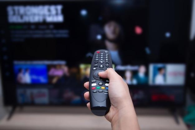 Zbliżenie Dłoni Za Pomocą Zdalnego Telewizora Smart Tv Na Niewyraźnym Telewizorze Smart Tv Z Wideo Na żądanie Premium Zdjęcia