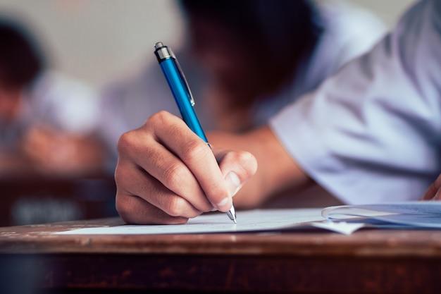 Zbliżenie do gospodarstwa ołówkiem i pisanie egzaminu końcowego Premium Zdjęcia