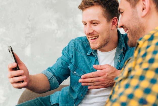 Zbliżenie dwóch przyjaciół płci męskiej siedzi razem oglądać na telefon komórkowy Darmowe Zdjęcia