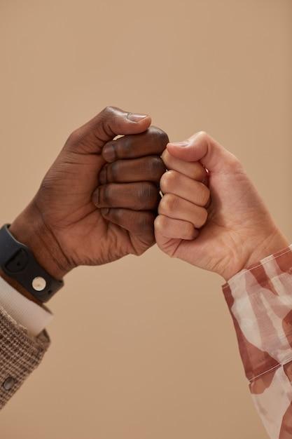 Zbliżenie: Dwóch Przyjaciół Witających Się Nawzajem Na Białym Tle Na Beżowej ścianie Premium Zdjęcia