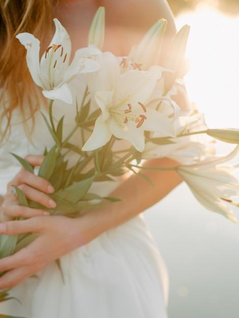 Zbliżenie Dziewczyna W Białej Sukni Trzyma Bukiet Białe Leluje. Przeciw Jezioru Premium Zdjęcia