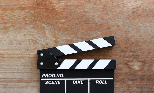 Zbliżenie filmu clapper deska na drewno stole z miękką ostrością i nadmiernym światłem w tle Premium Zdjęcia