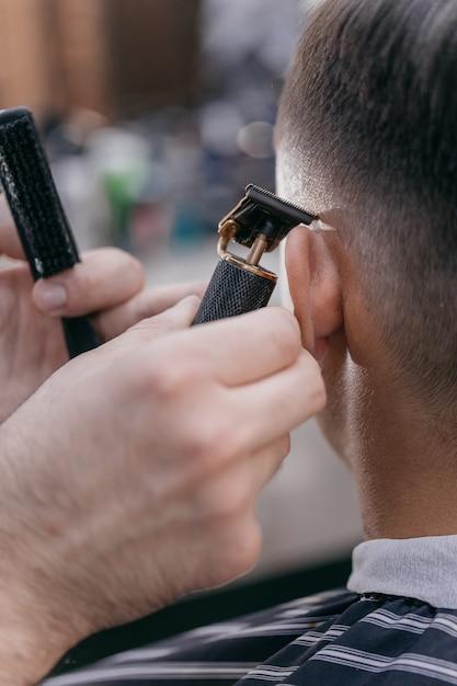 Zbliżenie Fryzjer ścina Włosy Faceta Maszynką Do Strzyżenia Premium Zdjęcia
