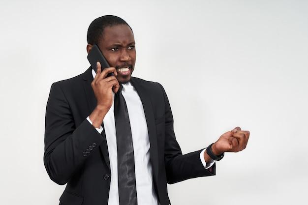 Zbliżenie Gniewny Młody Afrykański Mężczyzna Krzyczy Podczas Gdy Opowiadający Na Smartphone Premium Zdjęcia