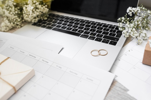 Zbliżenie kalendarza; obrączki ślubne; oddech dziecka kwiaty i laptop na biurku Darmowe Zdjęcia