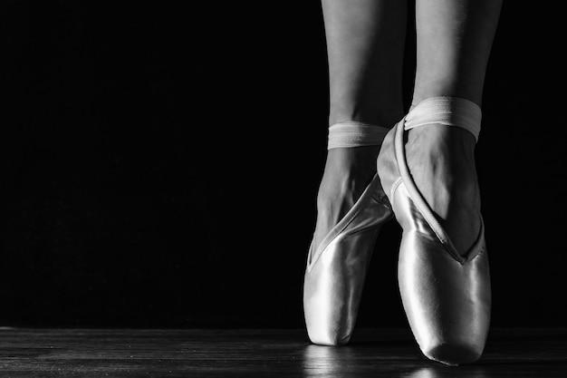 Zbliżenie klasycznych nóg baletnicy w pointes na czarnej podłodze Premium Zdjęcia