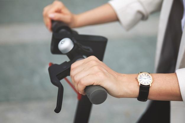 Zbliżenie: Kobiece Dłonie I Kierownica Skutera Elektrycznego Premium Zdjęcia
