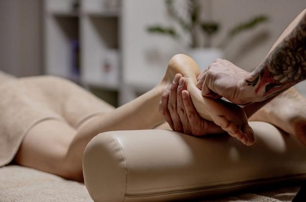 Zbliżenie: Kobiece Dłonie Robi Masaż Stóp Premium Zdjęcia