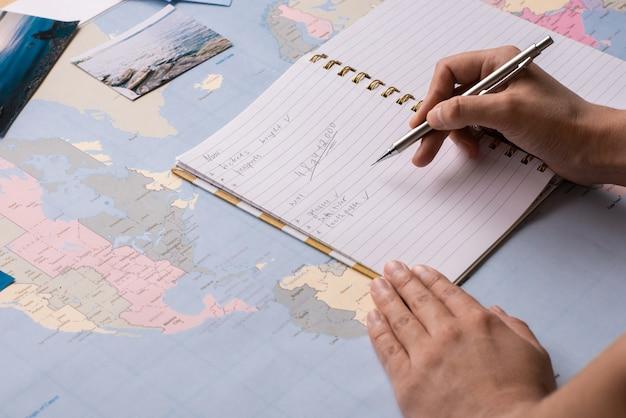 Zbliżenie: Kobieta Sprawdzająca Listę W Notatniku Podczas Przygotowań Do Podróży Premium Zdjęcia