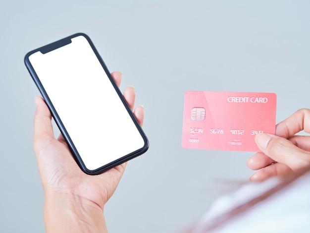 Zbliżenie: Kobieta Trzyma Telefon Komórkowy, Pusty Ekran I Kredytową Kartę Bankową Na Szarym Tle Premium Zdjęcia