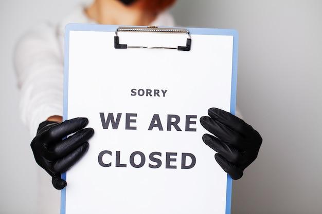 Zbliżenie Kobiety Trzymającej Puste Z Napisem Jesteśmy Zamknięci Wzywając Do Zaprzestania Rozprzestrzeniania Covid-19. Premium Zdjęcia
