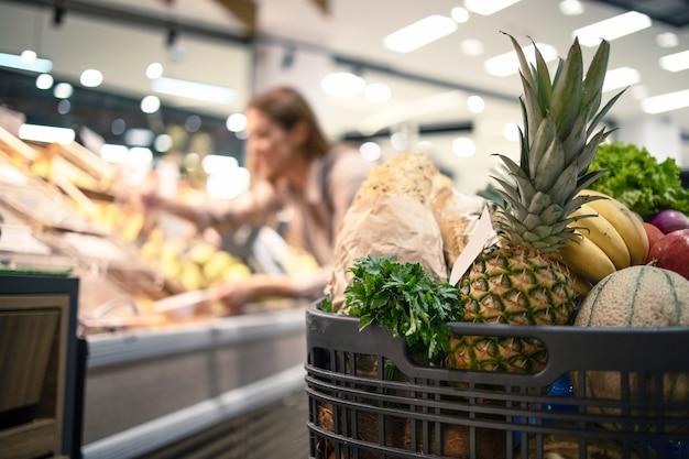 Zbliżenie Koszyka W Supermarkecie Pełnym żywności, Owoców I Warzyw, Podczas Gdy W Tle Kobieta Zdejmuje Produkt Z Półek Darmowe Zdjęcia