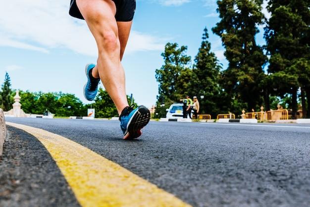 Zbliżenie kroku biegacza biegającego po asfalcie od pięty Premium Zdjęcia