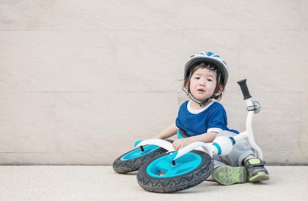 Zbliżenie ładny Dzieciak Siedzi Na Marmurowej Podłodze I Płacze Z Powodu Spadającego Roweru Na Parkingu Premium Zdjęcia
