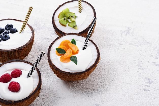 Zbliżenie Lody W Czterech Misach Kokosowych Z Jagodami Na Białym Tle Premium Zdjęcia