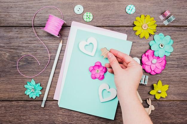 Zbliżenie ludzkiej ręki dekorowanie karty z pozdrowieniami na drewniane biurko Darmowe Zdjęcia