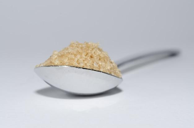 Zbliżenie łyżką Cukru Brązowego Na Białej Powierzchni Darmowe Zdjęcia