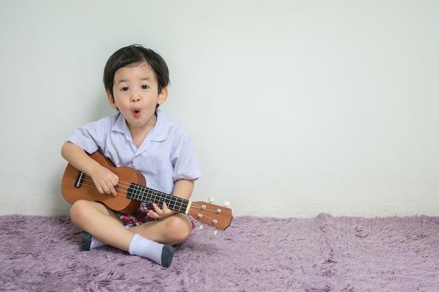 Zbliżenie małe dziecko w studenckim mundurze bawić się ukulele na dywanie z kopii przestrzenią Premium Zdjęcia
