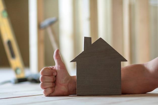 Zbliżenie Małego Drewnianego Modelu Domu Dłoni Mężczyzny Z Kciukiem Gest I Niewyraźne Obrazy Narzędzi Budowlanych. Inwestycje W Nieruchomości I Własność Wymarzonego Domu. Premium Zdjęcia