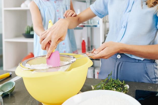 Zbliżenie Matki Pokazującej Córce W Wieku Preteen, Jak Przesiać Mąkę Podczas Wyrabiania Ciasta Premium Zdjęcia
