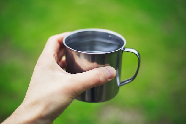 Zbliżenie: Męskiej Ręki Trzymającej Stalowy Kubek Z Wodą Na Niewyraźne Tło. Premium Zdjęcia