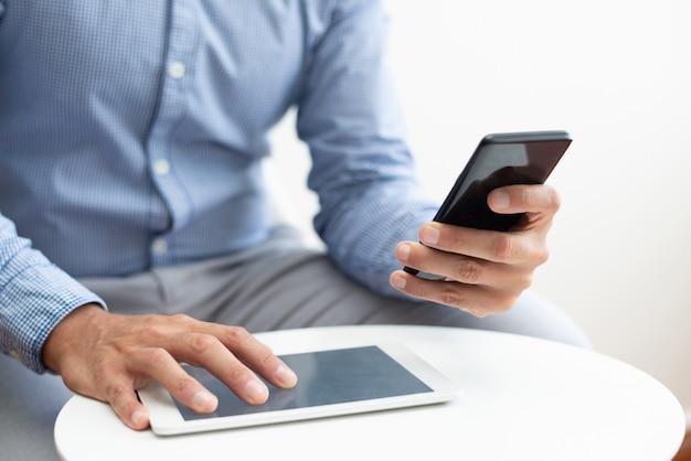 Zbliżenie mężczyzna używa smartphone i pastylkę przy stolik do kawy Darmowe Zdjęcia