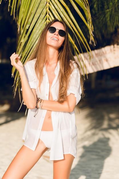 Zbliżenie: Młoda Seksowna Szczupła Dziewczyna Stojąca Na Plaży Na Sobie Białe Bikini Z Zielonym Liściem Palmowym. Nosi Białą Koszulę I Ciemne Okulary Przeciwsłoneczne. Jest Opalona I Stylowa Darmowe Zdjęcia