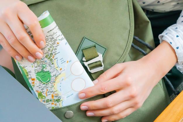 Zbliżenie Młodych Dziewczyn Ręki Stawia Mapę W Plecaku. Zielona Torebka Hipster Na Podróż. Koncepcja Turystyczna. Darmowe Zdjęcia