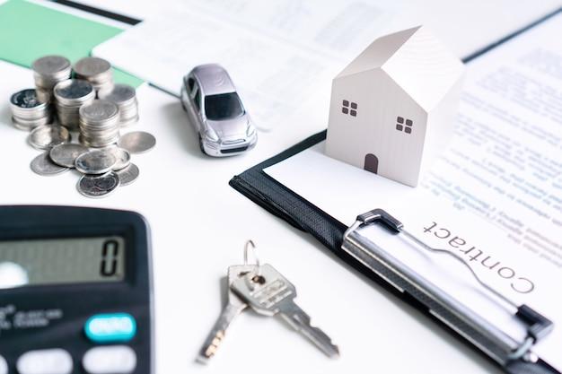 Zbliżenie: Model Domu I Samochodu, Dokumenty, Pieniądze I Kalkulator Na Białym Stole Premium Zdjęcia