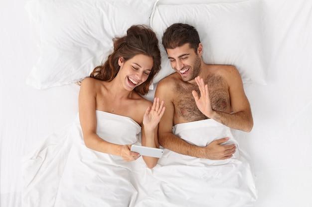 Zbliżenie Na Parę Leżącą W łóżku Pod Białym Kocem Darmowe Zdjęcia