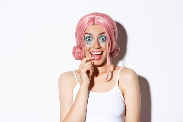 Zbliżenie Na Podekscytowaną Imprezową Dziewczynę W Różowej Peruce I Jasnym Makijażu, Wyglądającą Na Pod Wrażeniem, Uśmiechniętą I Wpatrującą Się Zdziwioną, Stojącą. Darmowe Zdjęcia