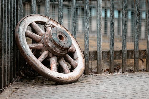 Zbliżenie Na Stare Drewniane Koło Na Ziemi Przed Płotami Pod światłami Darmowe Zdjęcia