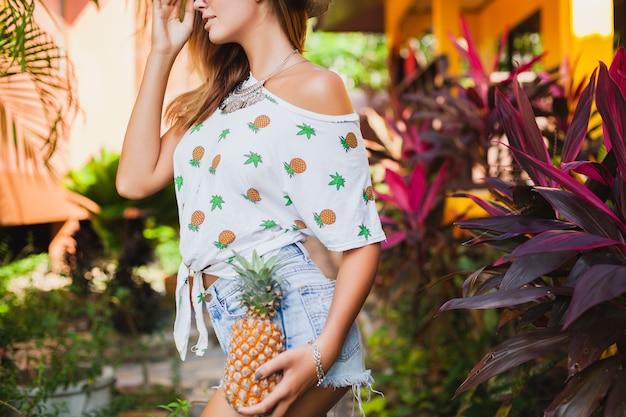 Zbliżenie Nogi I Biodra Smukłe Ciało Opalona Skóra Atrakcyjnej Kobiety Na Wakacjach W Słomkowym Kapeluszu Boso W Dżinsowych Szortach Z Nadrukiem T-shirt Letnia Moda, Ręce Trzymające Ananas Darmowe Zdjęcia