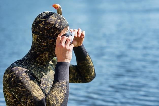 Zbliżenie nurek w kombinezonie z maską i fajka przygotować się do nurkowania w wodzie Premium Zdjęcia