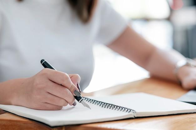 Zbliżenie Obraz Kobiecej Dłoni Pisania Na Notebooku Za Pomocą Pióra, Siedząc Przy Stole. Premium Zdjęcia