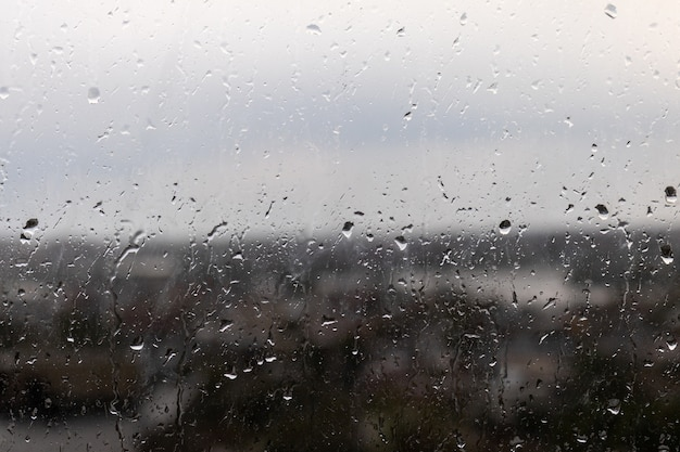 Zbliżenie Okna W Deszczowy, Ponury Dzień, Krople Deszczu Toczące Się Po Oknie Darmowe Zdjęcia