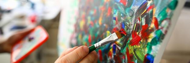 Zbliżenie Osób Ręcznie Malujących Na Płótnie Przy Użyciu Pędzla Z Kolorem Czerwonym. Abstrakcyjne Grafiki. Fragment Arcydzieła. Twórcza Koncepcja Hobby I Sztuki Premium Zdjęcia