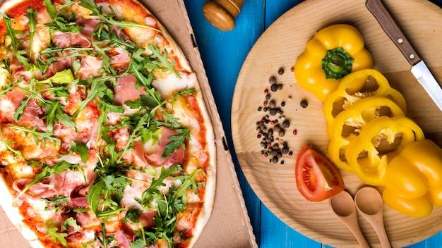 Zbliżenie Pizzy Z Boczkiem I Rukolą Pozostawia W Pobliżu Plastry Papryki; Pomidor; Czosnek I Przyprawy Na Stole Darmowe Zdjęcia