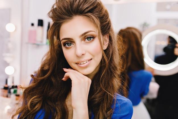 Zbliżenie Portret Młodej Kobiety Radosnej W Niebieskiej Koszuli Z Długimi Włosami Brunetka, Wyrażając Pozytywne Emocje Do Aparatu W Gabinecie Kosmetycznym Darmowe Zdjęcia