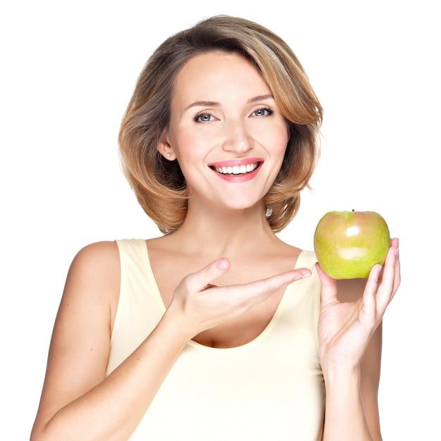 Zbliżenie Portret Młodej Pięknej Kobiety Uśmiechnięta, Wskazując Na Jabłko - Na Białym Tle. Darmowe Zdjęcia