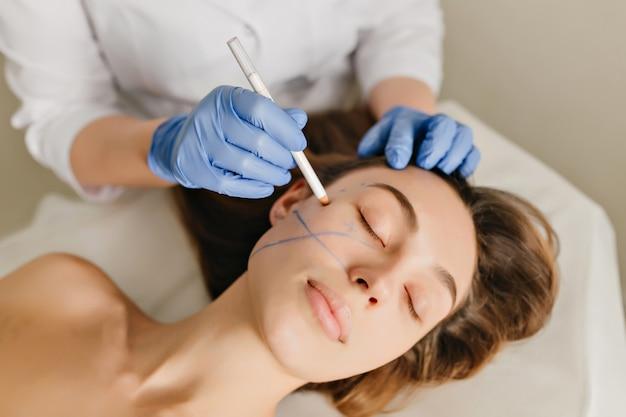 Zbliżenie Portret Pięknej Kobiety Podczas Przygotowań Do Terapii Kosmetologicznej W Gabinecie Kosmetycznym. Profesjonalne Zabiegi Dermatologiczne, Liftingi, Odmładzanie Darmowe Zdjęcia