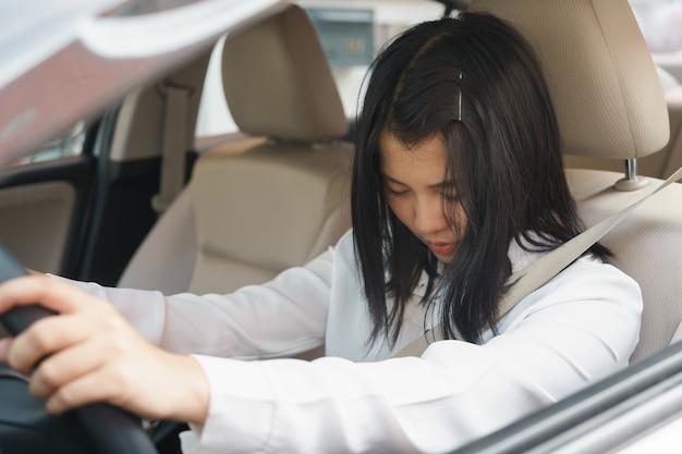 Zbliżenie portret śpiący, zmęczony, blisko oczy młoda kobieta jazdy jej samochód po długiej godzinie tri Premium Zdjęcia