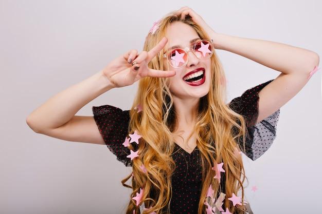Zbliżenie Portret Wesoła Dziewczyna Z Blond Kręconymi Włosami, świetnie Się Bawić Na Imprezie, Zabawę, świętowanie, Pokazując Pokój. Miała Na Sobie Czarną Sukienkę, Różowe Stylowe Okulary. Odosobniony.. Darmowe Zdjęcia
