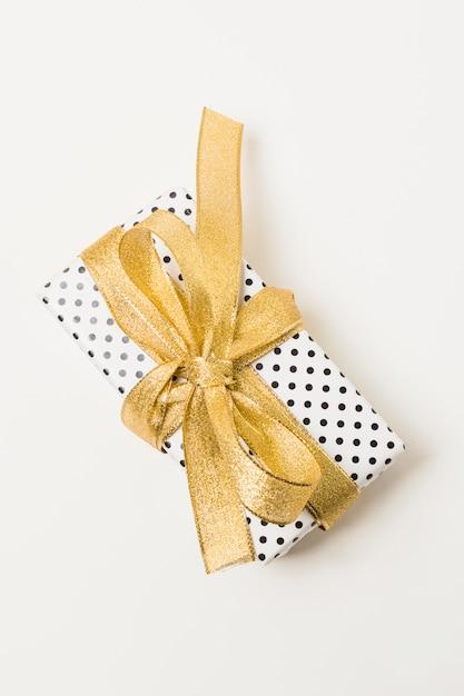 Zbliżenie: prezent zawinięty w kropkowany papier ozdobiony złotą wstążką na białym tle w tle Darmowe Zdjęcia