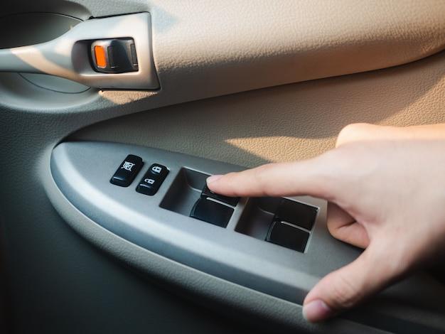 Zbliżenie ręka kierowcy naciskając przycisk sterowania oknem samochodowym. Premium Zdjęcia