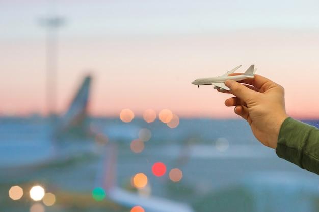 Zbliżenie Ręka Trzyma Zabawkarskiego Samolotu Model Przy Dużym Lotniskowym Tła Lotniskiem Premium Zdjęcia