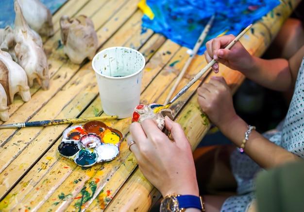 Zbliżenie ręki studenci sztuki trzyma farby muśnięcie studiuje i uczy się farbę na drewnianej zwierzęcej lalce w sztuki sala lekcyjnej. Premium Zdjęcia